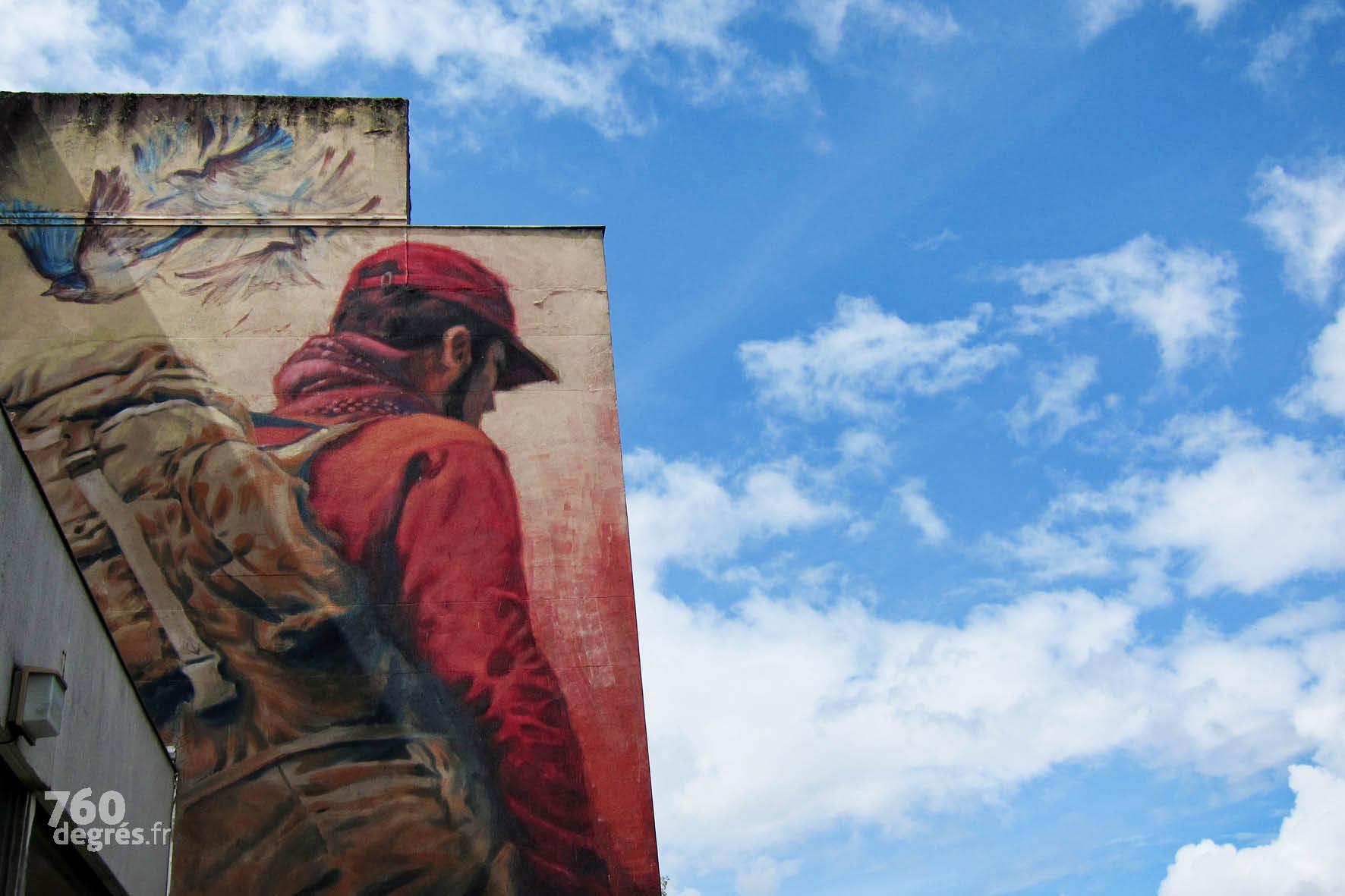 """ALINIZ (Allemagne) """"Le migrant et la liberté"""" - Cette peinture, réalisée uniquement à la patte de lapin, s'inspire d'une photo prise par l'artiste lors de son arrivée à Paris : en chemin pour sa résidence à Street Art City en 2016, il assiste impuissant à l'arrestation de jeunes migrants Syriens en gare de Lyon avec qui il avait fait le voyage."""